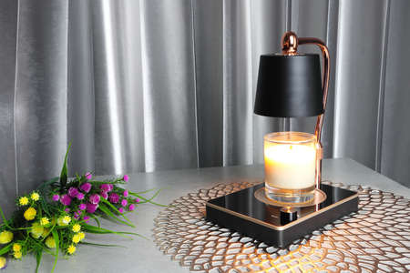 The luxury lighting aromatic scent clear color glass candle is put on the electric candle warmer on the grey table near the grey curtain in the bedroom