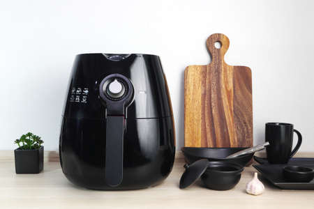 a black deep fryer or oil free fryer appliance, mug, dish and wooden tray are on the wooden table in the kitchen with a small plant in the pot ( air fryer ) with background of white cement wall Standard-Bild