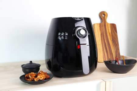 a black deep fryer or oil free fryer appliance, mug, dish and wooden tray are on the wooden table in the kitchen  with a dish of fried chicken wings on the background of white cement wall Banque d'images