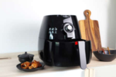 the blur photo of a black deep fryer or oil free fryer appliance, mug, dish and wooden tray are on the wooden table in the kitchen  with a dish of fried chicken wings