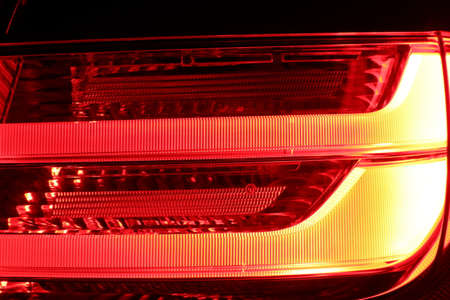 The close up photo of led right tail light of the sports luxury car in the dark garage
