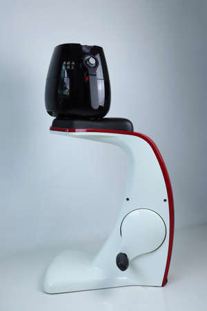 black air fryer is on exercise spinning bike machine with the white cement wall background of the gym, in ads concept of