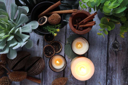 aromatic scented candles glasses are on the wooden table with various plants , herbs and spices in the living room of the cottage during Christmas party new year celebration