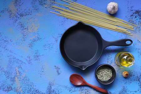 cast iron pan , raw pasta sticks, garlic, rosemary , herbs and olive oil and wooden spoon on the blue background, view from the above in the nice kitchen