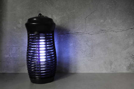 the insects mosquito electric killer blue light lamp is put on the grey table in the dark bedroom with cement wall background for better sleeping ambient condition for every one of the family members