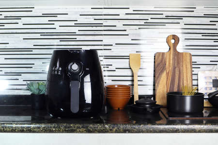 a black deep fryer or oil free fryer , air fryer appliance, is on the black marble table in the nice interior design kitchen of the house Stockfoto