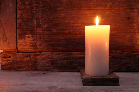 the burning luxury aromatic scented pillar candle glass are on the wooden table with background of the vintage wooden wall of the cottage in the living room during christmas party celebration