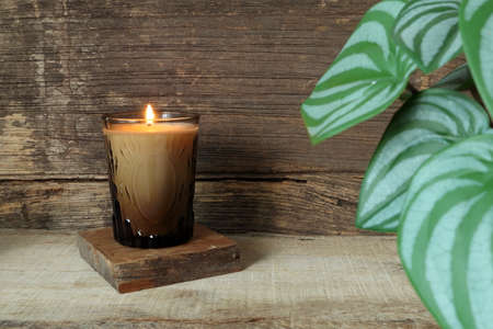 the burning luxury aromatic scented candle glass on the wooden table with background of the vintage wooden wall of the cottage in the living room during christmas party celebration