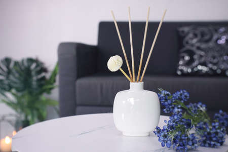 luxury aroma scented reed diffuser ceramic vase is used as room freshener and decoration items on the white marble table with bouquet of flowers in the living room to creat romantic valentine ambient Stock Photo