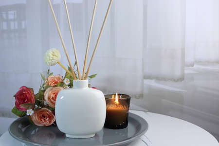 luxury aroma scent reed diffuser ceramic vase is on white marble table with glass of scented candle on white curtain background to creat romantic and relax ambient in bedroom on happy valentine day