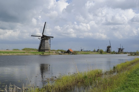 windmill parade, kinderdijk, netherlands        row of windmills at world famous touristic location, shot under a stormy bright spring sky