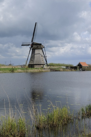 location shot: windmill and canal, kinderdijk, netherlands           windmill at world famous touristic location, shot under a stormy bright spring sky
