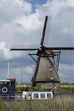 location shot: windmill and boat, kinderdijk, netherlands      windmill at world famous touristic location, shot under a stormy bright spring sky while a boat passes by Stock Photo