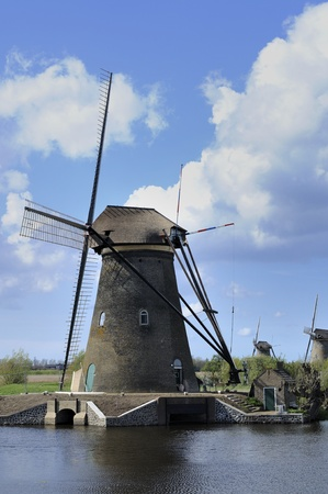 location shot: windmill at kinderdijk, netherlands      windmill at world famous touristic location, shot under a stormy bright spring sky