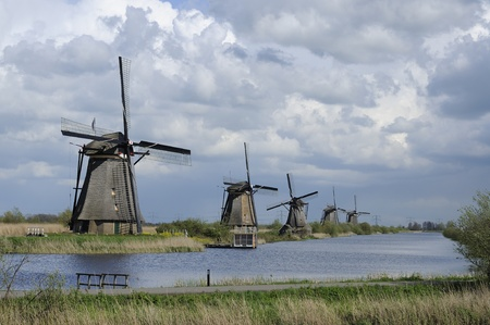 location shot: windmills before storm, kinderdijk, netherlands    row of windmills at world famous touristic location, shot under a stormy bright spring sky Stock Photo