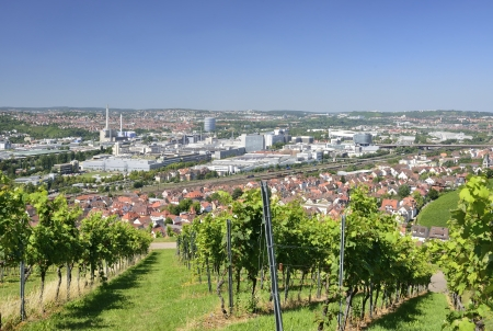 vineyards and industrial settlements, Stuttgart, Germany, 2012, 1 of August  Cityscape with sharp contrast between old traditional houses, large industrial plants and hilly landscape with vineyards  In distance the city stadium and parks around it