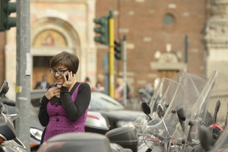 woman in San Babila  2, Milan, young woman makes her way among scooters parked in city center, in the same time is using a cellphone and smiles notwithstanding the chaos Stock Photo - 18068464