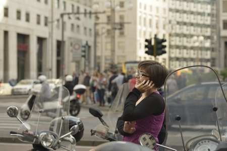 young woman in San Babila traffic, Milan, young woman makes her way among scooters parked in city center, in the same time is using a cellphone and smiles notwithstanding the chaos Stock Photo - 18068462