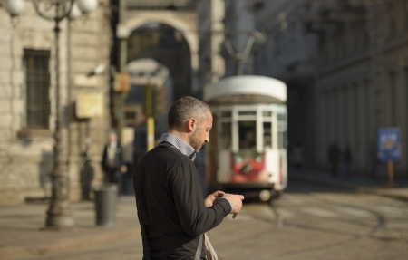 man and incoming tram, Milan, man looking at his smartphone while walking in city center, in background the blurred shape of a tram and of the galleria Stock Photo