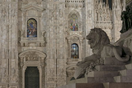 Minster illuminated windows and leo, Milan, illuminated facade and decorated glass windows of cathedral  at night, in foreground foreshortening of leo statue in middle of minster square photo
