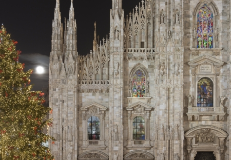 Minster illuminated windows and Xmas tree, Milan, illuminated facade and decorated glass windows of cathedral  at night under moon, in foreground foreshortening of Christmas tree photo