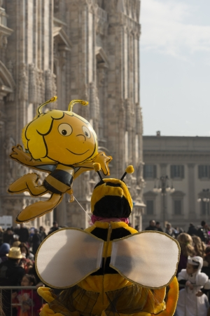 dressing up costume: little bees out of the Minster, MILAN, ITALY - FEBRUARY 16: a  dressed up child and his bee balloon, in background blurred Minster. Shot at Kid Editorial