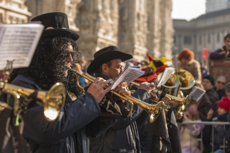 brass line in parade,  MILAN, ITALY - FEBRUARY 16: brass players of a band in parade, in background blurred Minster. Shot at Kid