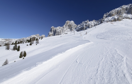 bright snow on Laurin ski run and Rosengarten, Costalunga pass; steep ski run in Dolomites under rock cliffs of famous mountain range, shot in bright light under deep blue sky Stock Photo