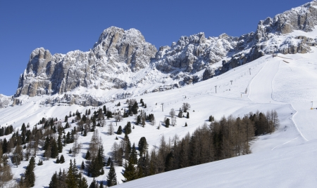ski runs: ski runs and Rosengarten, Costalunga pass; ski runs and chair lift in Dolomites under rock cliffs of famous mountain range, shot in bright light under deep blue sky