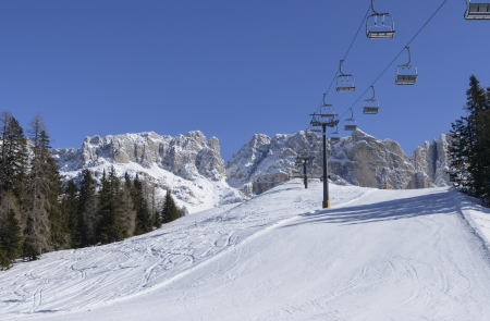 chair lift: ski run and chair lift at Rosengarten, Costalunga pass; foreshortening of ski area in Dolomites under rock cliffs of famous mountain range, shot in bright light under deep blue sky