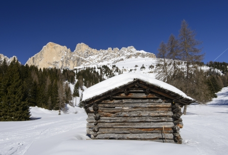 Rosengarten and wooden hut, Costalunga pass; little wooden huts in Dolomites under rock cliffs of famous mountain range, shot in bright light under deep blue sky