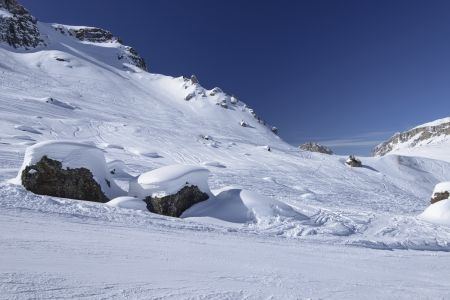 snowy stones, Arabba; bright snow forms smooth waves on stones in slope in Dolomites, shot under deep blue sky photo