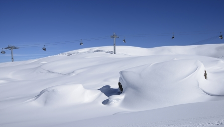 snow waves and chair lift, Arabba; bright snow covers stones in slope in Dolomites in background chair lift, shot under deep blue sky photo