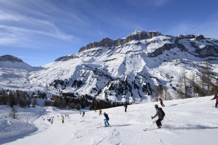 descending toward Pordoi pass, Arabba; skiers on bright snow over steep ski run in Dolomites in important ski area