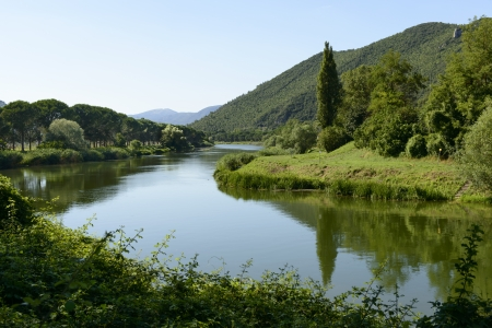 Piediluco canal toward Marmore falls, Rieti; view of the artificial canal in the green Rieti valley that connects Piediluco lake and Marmore falls, shot in bright summer light