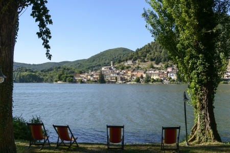 rieti: beach chairs on lakeside at Piediluco lake, Rieti; view of beach chairs on  lake shore in front of village in green Rieti valley, shot in bright summer light Stock Photo