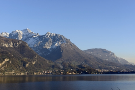 Grigna craggs on Como lake; landscape of eastern part of Como lake with the slopes of the important mountain reaching the shore , shot in bright winter light with the first snow on mountains photo