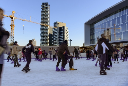 MILAN, ITALY - DECEMBER 30 blurred shapes of ice-skaters at small skating rink set for Holidays at new business hub, building site and skyscrapers in background on dec 30, 2013 Milan, Italy