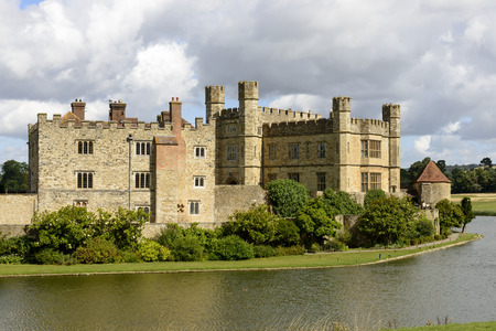 Leeds castle east side , Maidstone, England, view of the eastern side of medieval castle and its moat,  shot in bright light under a cloudy sky