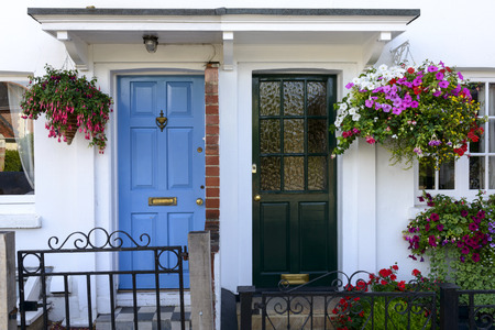 oxfordshire: blue and black terrace doors, Henley on Thames , painted doors of old terrace houses with blossoming flowers in central street of touristic village on river Thames Stock Photo
