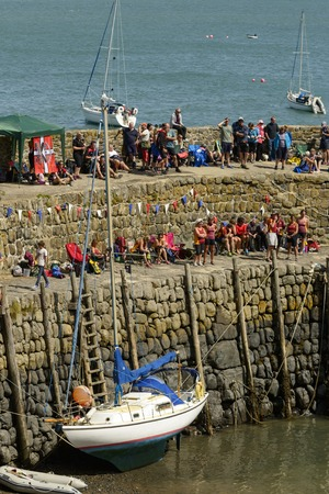 seawall: CLOVELLY, UNITED KINGDOM - AUGUST 16 viewers crowd the seawall of the harbor Copilot Gigs During The Regatta rowing competition, shot on 16 august 2014, Clovelly, Devon, United Kingdom