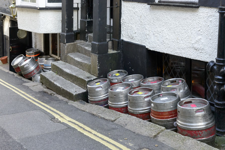 hoard: beer kegs in street, Falmouth, hoard of beer kegs  piled up by a street in the village on southern coast of Cornwall Stock Photo