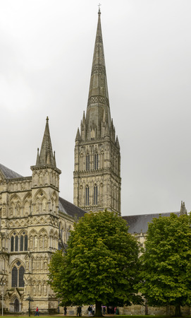 Cathedral bell-tower , Salisbury, view of huge bell-tower of famous Gothic church, shot under light rain with some unrecognisable tourists and their umbrellas around the church