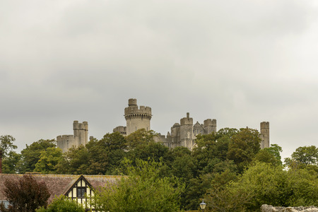 west sussex: Arundel castle skyline, West Sussex, view of the medieval castle out of the top of the trees that surround it,  shot in bright light under a cloudy sky , Arundel , West Sussex Editorial
