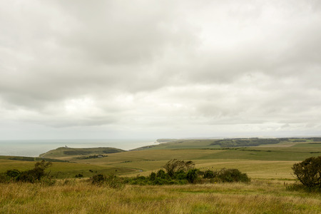 landscape of green Downs countryside with sea and coast in distance,  shot under bright cloudy sky near Eastbourne, East Sussex
