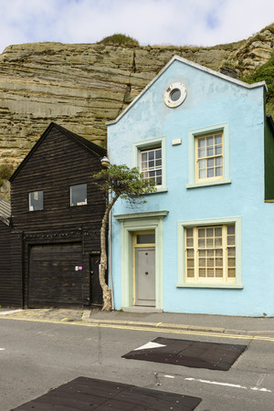 cottage under the cliff, Hastings, view of old buildings built just under the cliffs in historic touristic village of Hastings, East Sussex