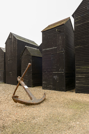 fish net: view of old anchor amid fish net huts built in wood and painted black in historic village of Hastings, East Sussex