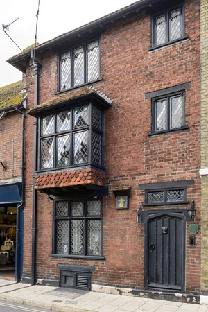 bow window: view of old brick house on a street in the historic village of Rye, East Sussex