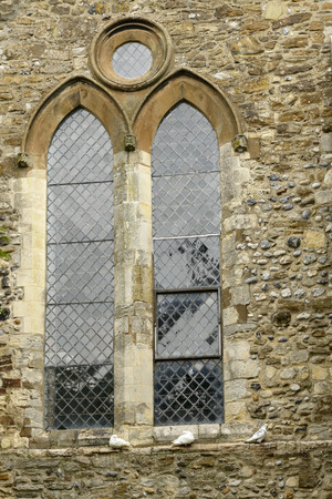 thomas stone: stained-glass window of St. Thomas curch, detail of a stanied-glass mullioned window of ancient stone church  in small  historic village of Rye, East Sussex