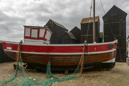 fish net: view of old fish boat amid fish net huts built in wood and painted black in historic village of Hastings, East Sussex